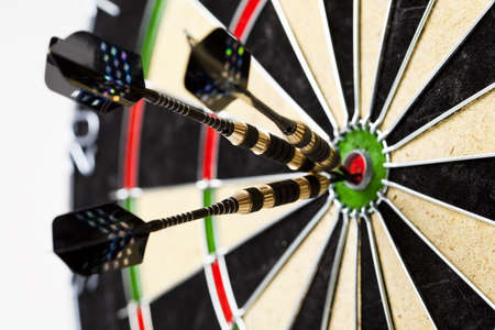 Dartboard with three darts in a bulls eye