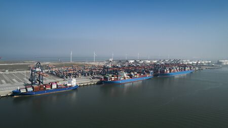 Photo pour Aerial view of container terminal in the harbor MAASVLAKTE, Netherlands. A large containership from Cosco is unloading - image libre de droit