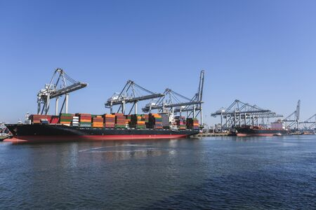 Photo pour Huge cranes and ships anchored at harbor. International commercial port, city of Rotterdam background. Logistics business - image libre de droit