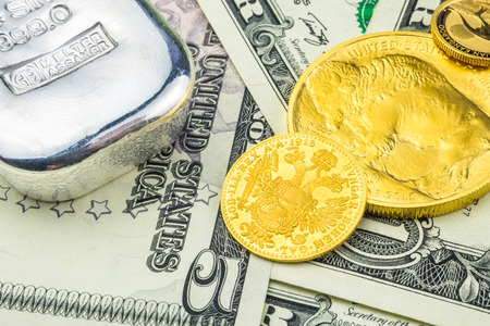 silver brick and golden coins laying on dollar banknotes