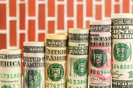 rising steps made of rolls of all american dollar banknotes in one row on red wall background