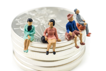 group of people miniature figurines sitting on silver american eagle coins on white background