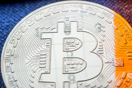closeup of golden bitcoin coin with a numbers reflection on its surface