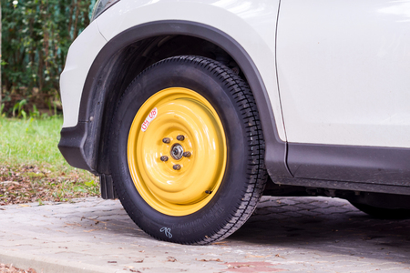 close-up of thin interim collapsible spare tyre fitted on white SUV car