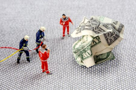 closeup of miniature figurines dressed like members of firemen special team interfering during gas and other chemical accidents with the action protecting/saving american dollar, the debt is rising without controll