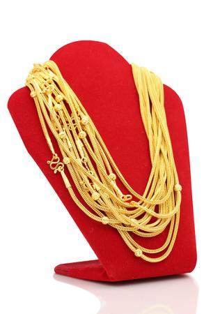 Foto de Gold necklaces on necklace display stand white background. - Imagen libre de derechos