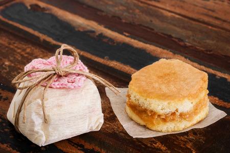 Brazilian wedding sweet bem casado sponge cake with crochet heart on wooden table  Selective focus