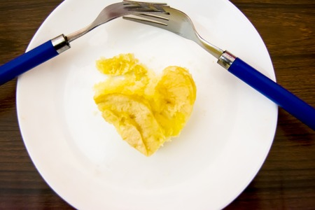 Piece of apple pie with heart shape and two forks interlaced on a wooden table