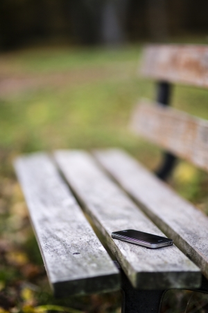 Someone forgot cell phone on a bench in the park