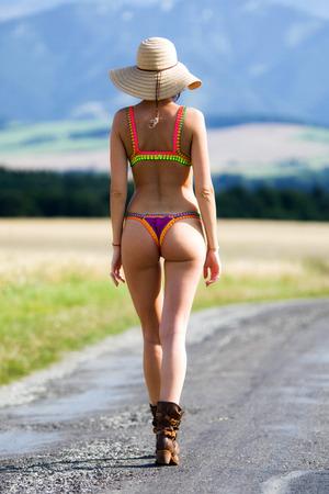 Outgoing girl with big sunhat and bikini.