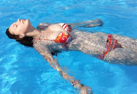 Photo pour Girl with perfect body and big boobs relaxing in the pool - image libre de droit