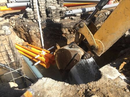 Photo pour Excavator is being used to stop the water after breaking a waterpipe during construction work - image libre de droit