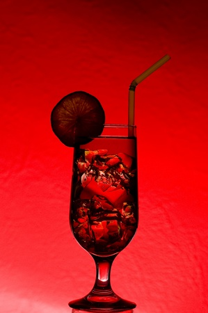Cocktail with and ice. Alcoholic drink on red background