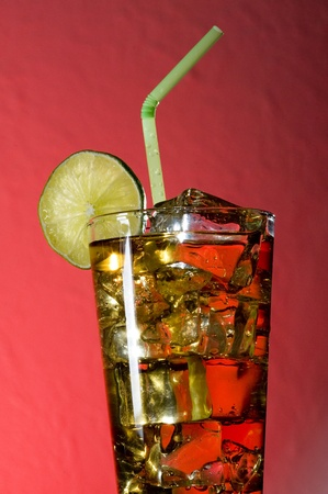 Cocktail with and ice.  Drink on red background