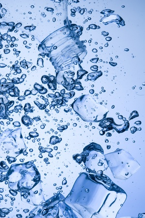 Mineral water with ice. Creative splashing blue water