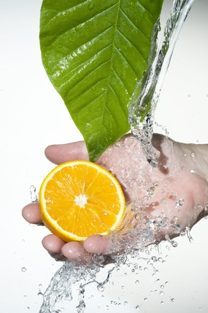 Flowing fresh water on the palm and orange