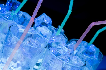 Glass of ice water on blue background. Cold de a alcoholic drink