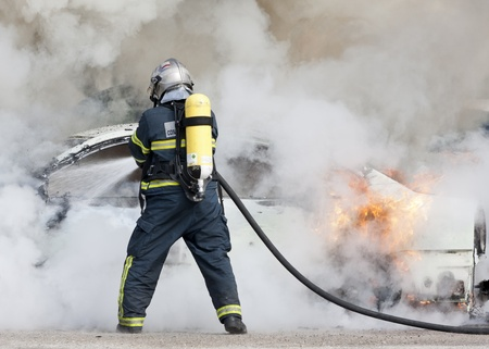 a firefighter putting out a car that was burning