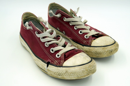 Dirty old torn vintage red canvas shoes Converse All Stars