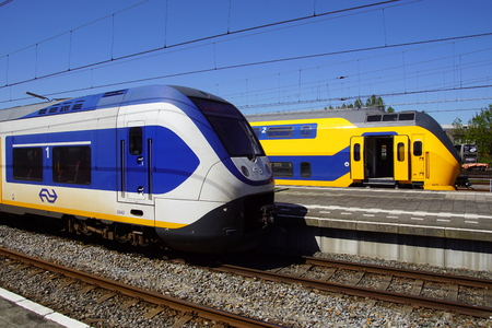 Two Dutch Railway (Dutch: Nederlandse Spoorwegen or NS) electric passenger trains Sprinter and Intercity standing at the railway station of the city of Hoorn.