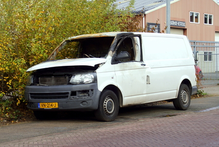 Photo for Naarden, the Netherlands - November 11, 2018: White burned out Volkswagen Transporter by the side of the road. Nobody in the vehicle. - Royalty Free Image