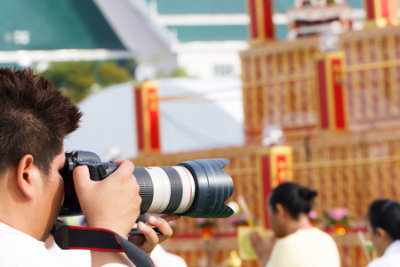 Young photographer man upholds his camera while shooting candid photo
