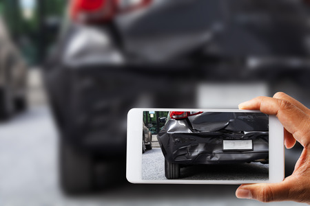 Photo for Car insurance agents take pictures of accident-damaged vehicles with a smartphone as a proof of insurance claim. - Royalty Free Image