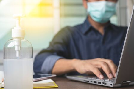 Photo pour Alcohol gel with male employee wearing a health mask Preventing corona virus infection covid-19 in back, concept of working from home and social distancing. - image libre de droit