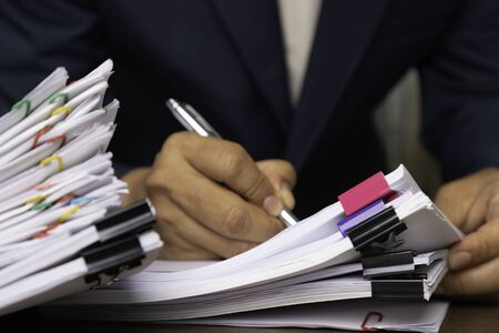 Photo pour Male office workers holding and writing documents on office desk, Stack of business paper. - image libre de droit