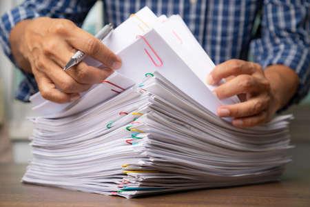 Photo pour Business man hand pick up Stack overload document report paper. - image libre de droit