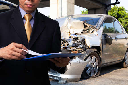 Photo pour Side view of insurance officer writing on clipboard while insurance agent examining silver car after accident. - image libre de droit