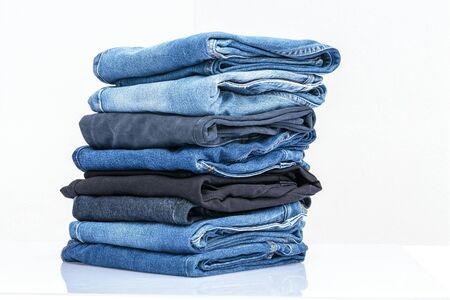 Photo pour Jeans trousers stack on white background - image libre de droit