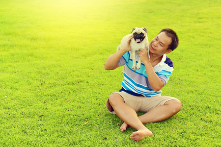 Happy Asian man playing with his dog in garden