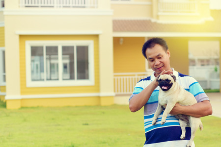 Happy Asian man playing with little Pug in garden
