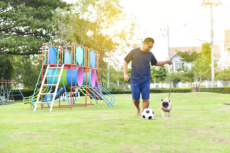Asian man playing football with brown Pug in garden