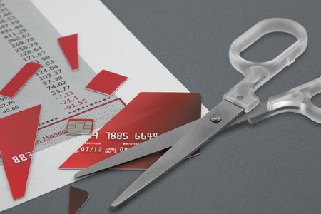 Cut up Credit Card and a pair Scissors on top of a Bank Statement