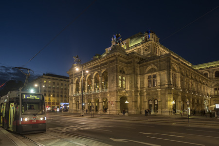Wide shot of traffic passing in front of the Vienna Opera House on Opernring. Taken early evening in September as the city lights are coming on