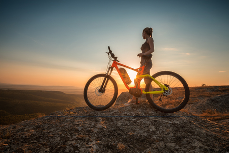 Photo for Sunset with a bike.  A woman with a bike enjoys the view of sunset over an autumn forest. - Royalty Free Image