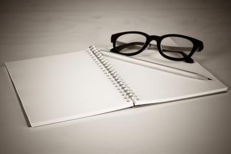 Photo pour Notebook with a pencil and eye glasses, Vintage effect - image libre de droit