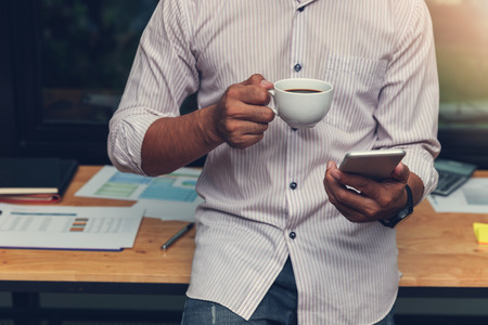 Foto de Business and finance concept of office working, Businessman using smartphone and holding coffee cup in office - Imagen libre de derechos