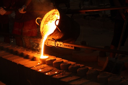 molten metal poured from ladle for casting