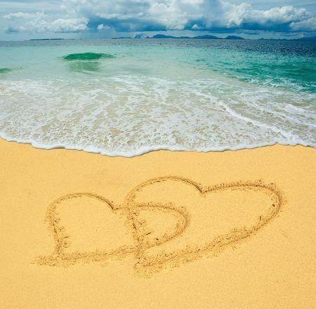 two hearts drawn in a sandy tropical beach