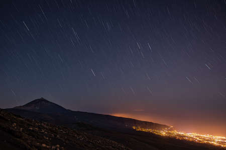 Photo pour mountain with stars where you can see the city illuminated with warm colors - image libre de droit