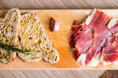 Spanish iberico ham with toasts on wood tableの写真素材