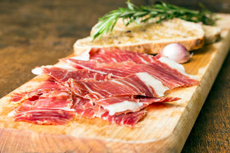 Spanish ham with toasts,rosemay,garlic and olive oilの写真素材