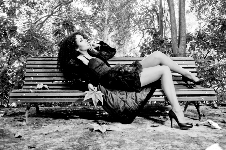 Young beautiful woman siting on bench in park