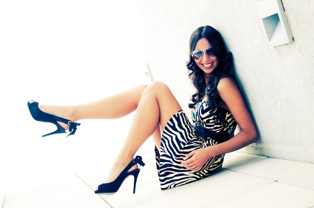 Photo for Funny female model at fashion with high heels sitting on the floor - Royalty Free Image