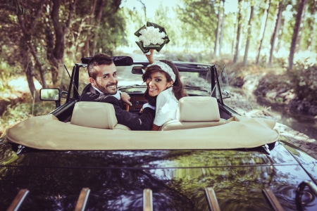 Foto de Just married couple together in an old car - Imagen libre de derechos