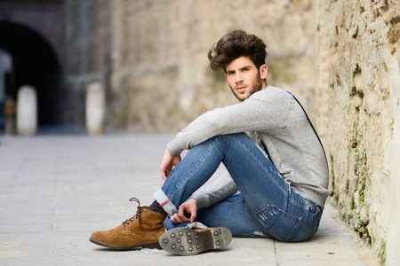 Foto de Portrait of young man wearing suspenders sitting on the floor in urban background - Imagen libre de derechos