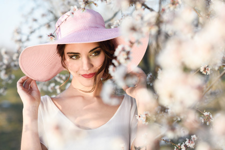 Foto de Portrait of young woman in the flowered field in the spring time. Almond flowers blossoms. Girl wearing white dress and pink sun hat - Imagen libre de derechos